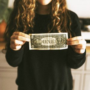 girl holding a one-dollar bill