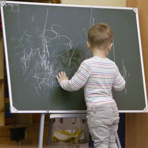 Little boy drawing on a chalkboard