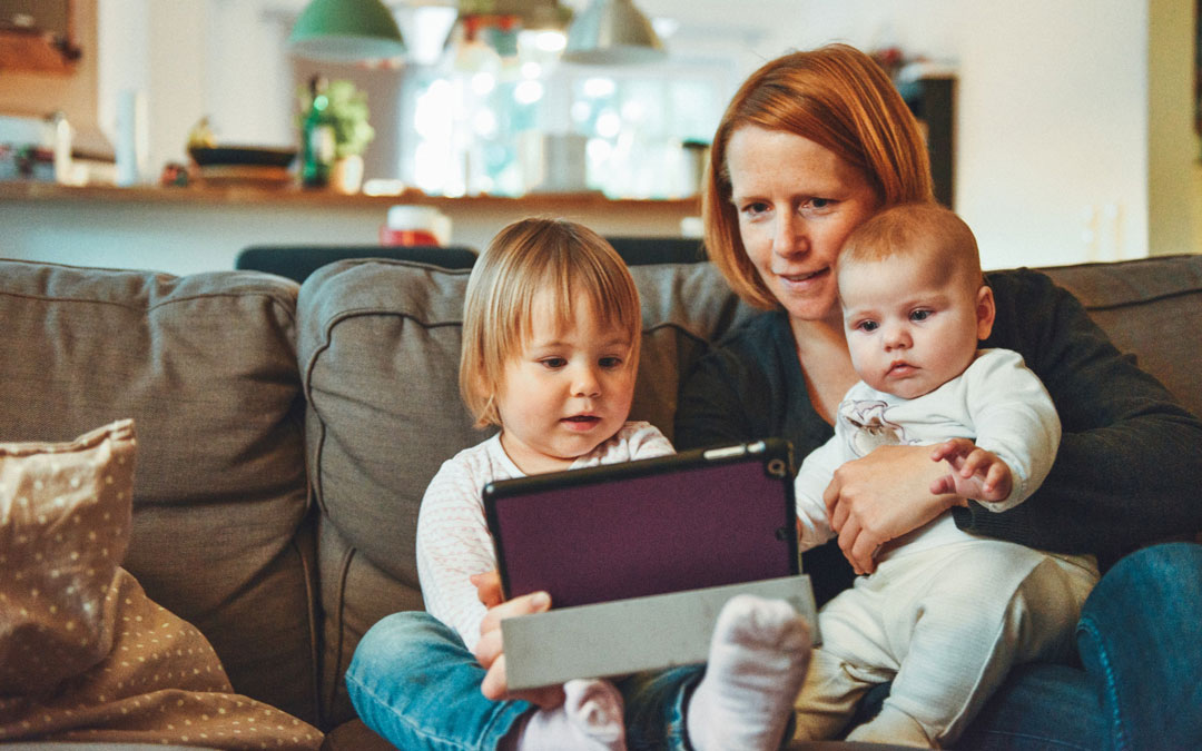 A mother sitting on a sofa while holding her two babies and an iPad